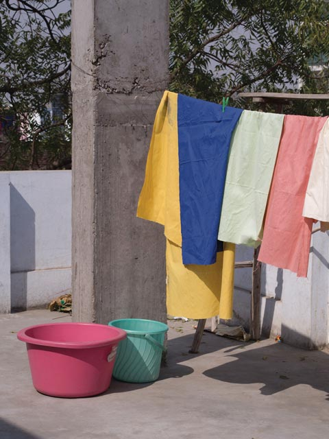 Colored Khadi fabrics hanging from a line before block printing. Image by All The Fruits.