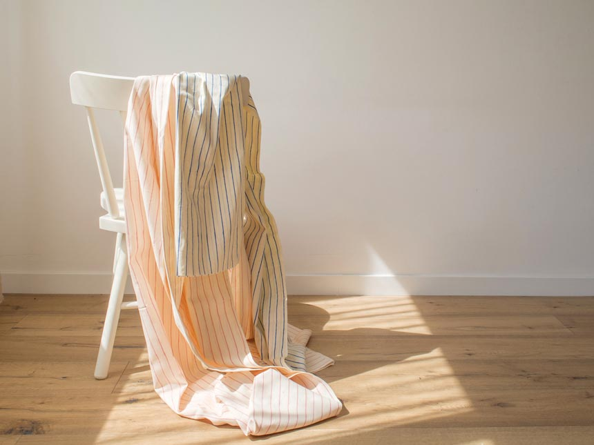 Beautiful linen fabrics hanging from a white wooden chair. Image by Allthefruits.