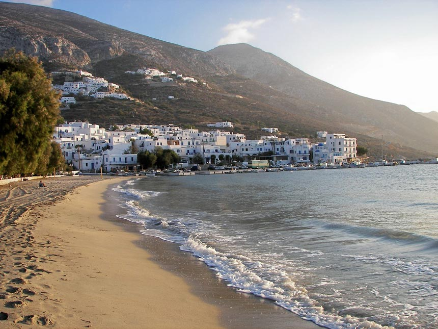 A view of the sandy beach of Aegiali with the seaside village in the background.
