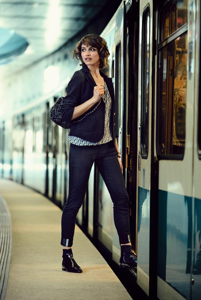 A stylish woman about to embark on a train, wearing black pants and a black blazer. Image by Betty and Co.