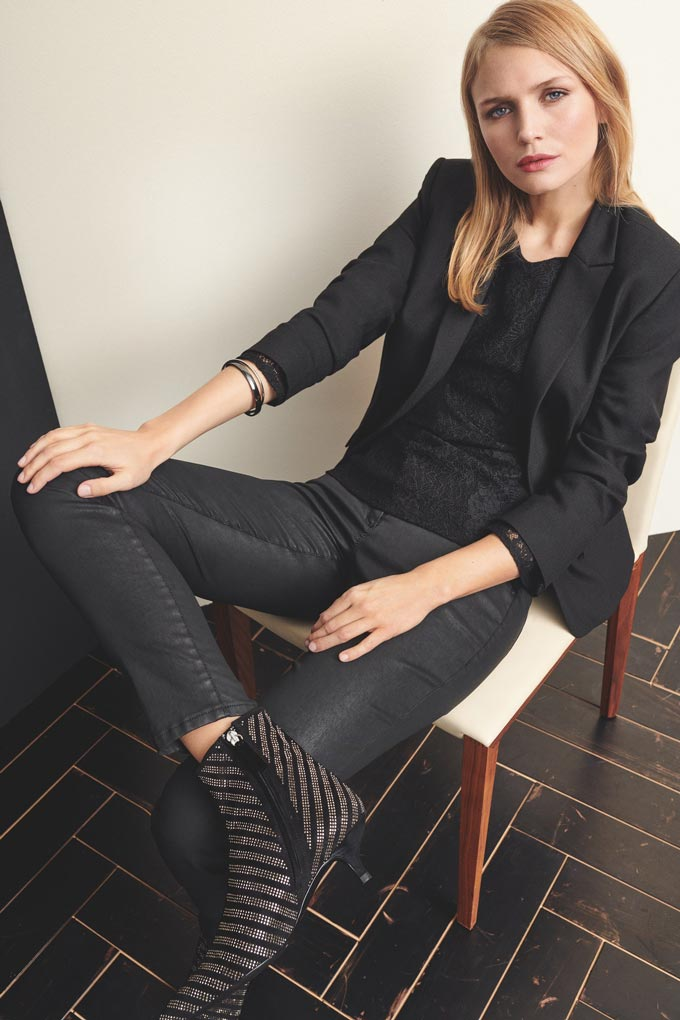 I love this sophisticated dress styling where this woman with blonde sleek hair, a black tee, black blazer, dark denim pants and black ankle boots has this look on her face - Really?! Image by Betty and Co.