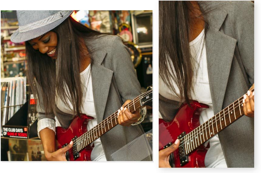A stylish woman dressed in a grey blazer, hat and white tee is trying an electric guitar in a music shop.