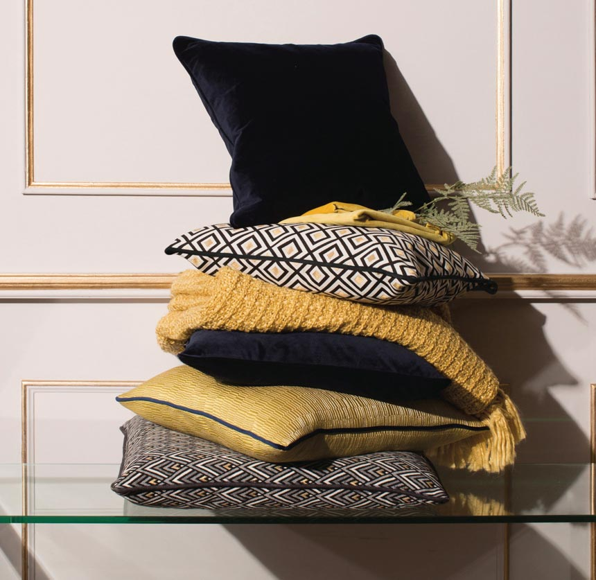 A stack of decorative ochre yellow, grey and black pillows with patterns on a glass table. Image by Harvey Norman.