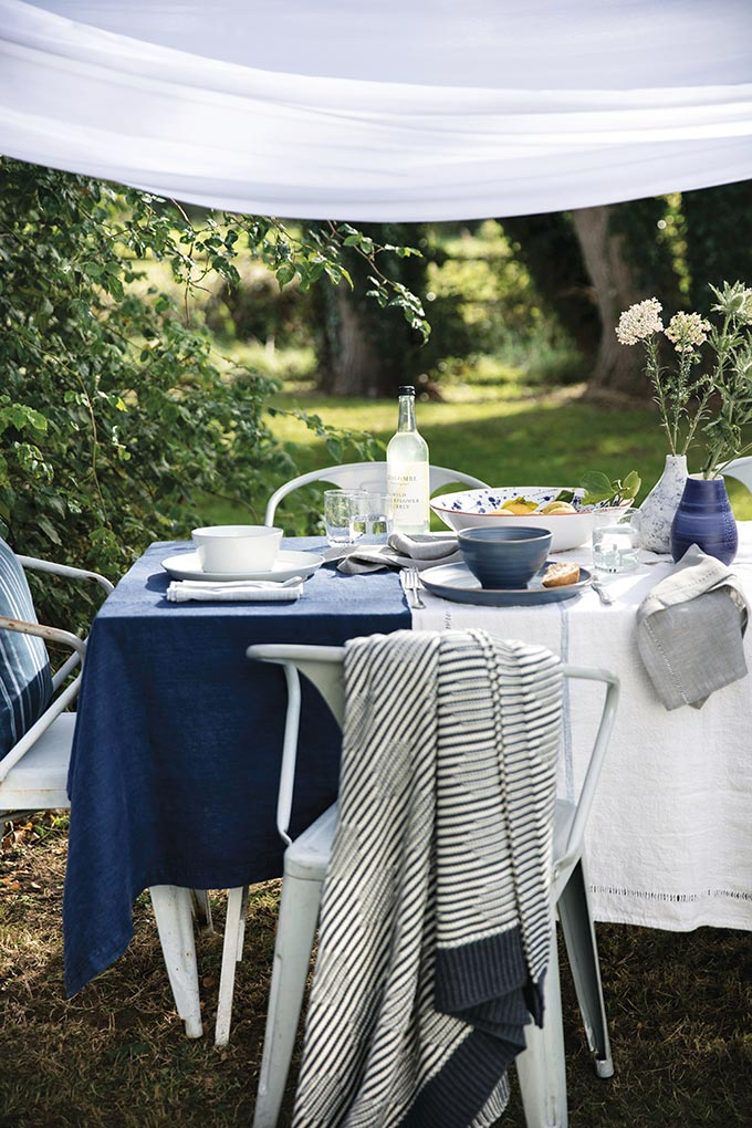 Partial view of a blue and white outdoor dining setup, styled beautifully. Image by House of Fraser.
