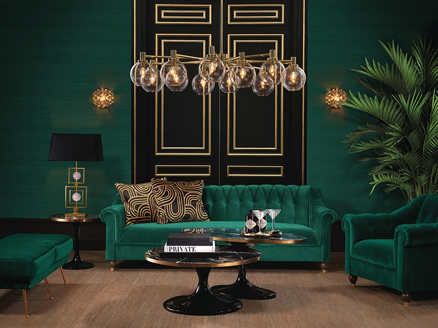 A luxurious sitting room with dark green walls and dark green velvet sofa and armchairs. Two black doors behind the sofa create a stunning accent backdrop. Image by Houseology.