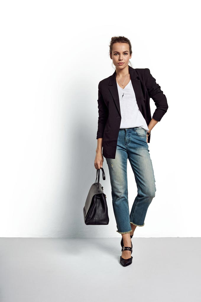 You can never go wrong with a white tee, blue denim pants, a black leather bag and shoes and a black blazer as styled by a young woman. How can you? Image by Hush.