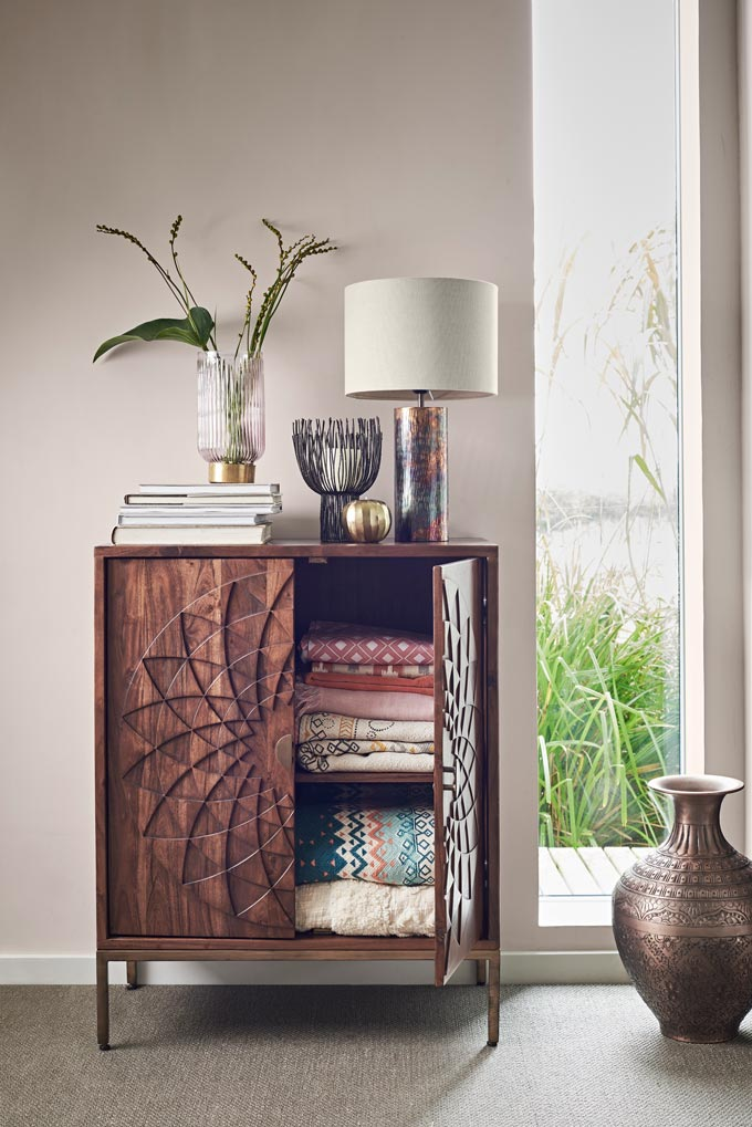 A dark wood stain cabinet with decor atop has one of its doors open enough to look inside and see stacks of textiles lined on the shelves. Image by John Lewis.