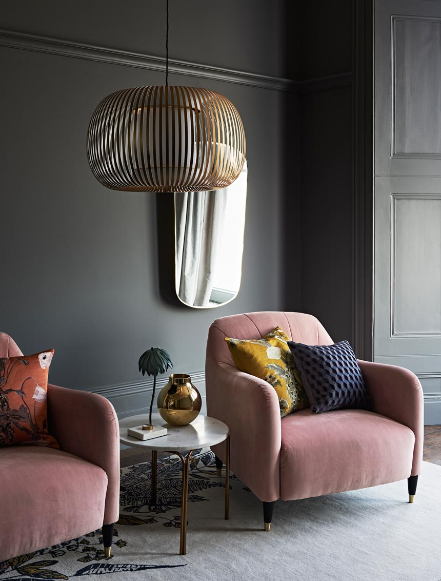 A moody but stylish sitting room with two pink velvet armchairs. I love the rectangular shaped mirror on the dark gray blue wall behind them. Image by John Lewis.