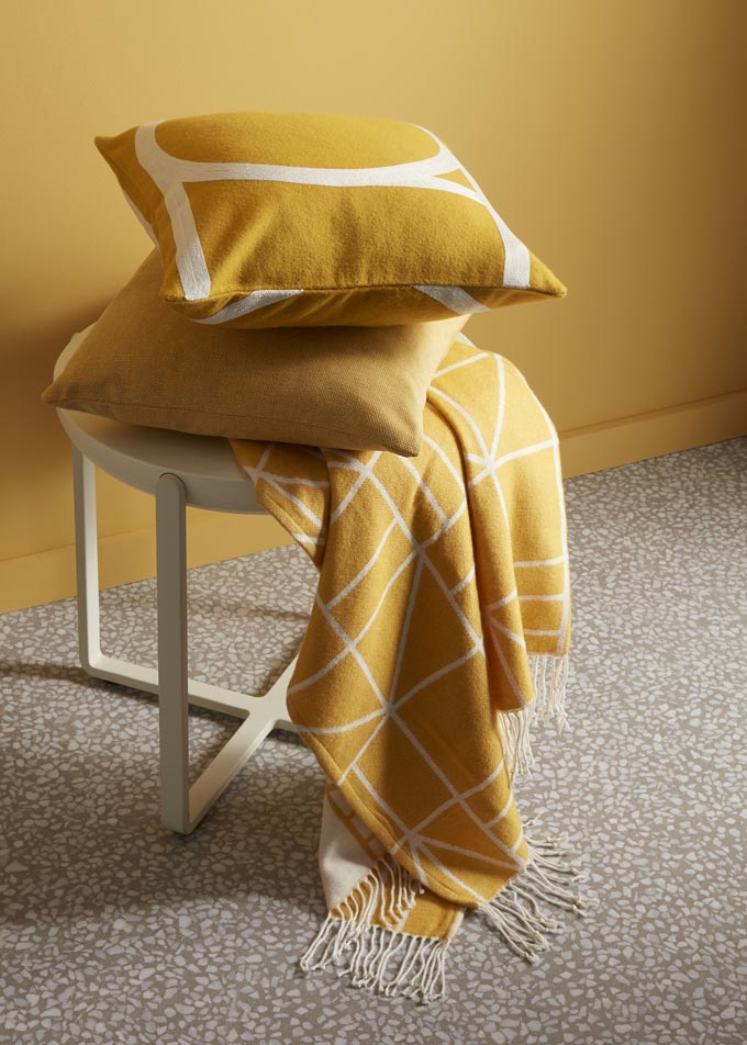 "Ochre seems to be this season's ""it"" color in textiles. Ochre decorative pillows, ochre throw on a light wood stain stool against an ochre accent wall. Image by John Lewis."
