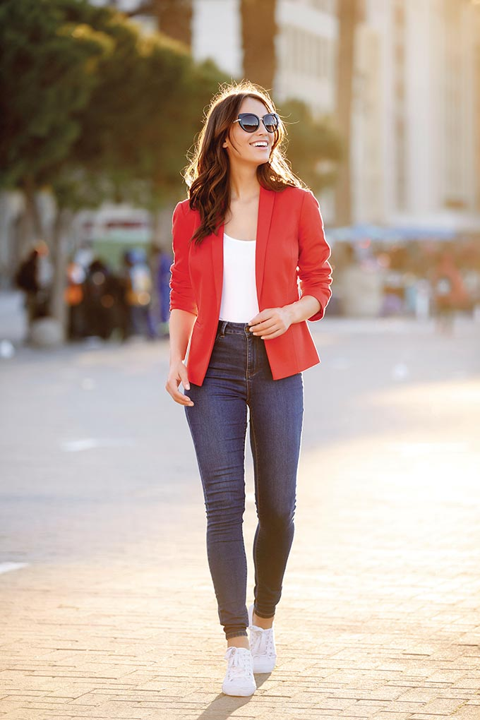 Simplicity at its best. A stylish woman walking down the street in a red blazer with a white tee and blue denim pants and sneakers. Image by M&Co.