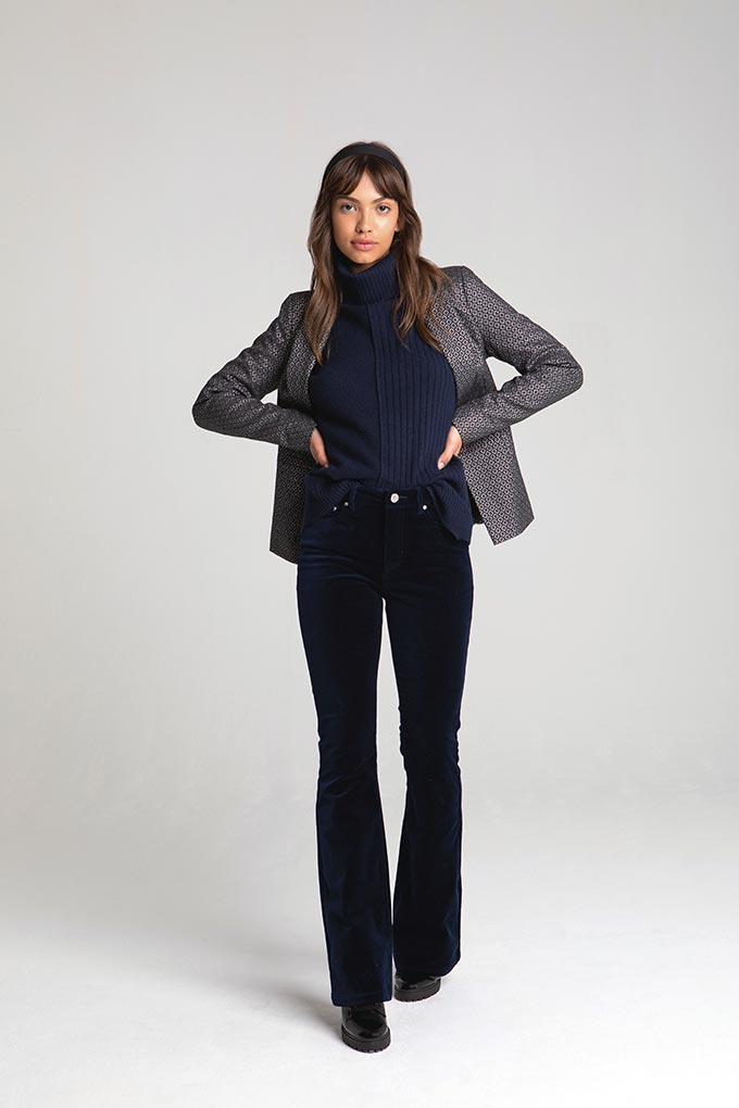 A woman dressed in an all black outfit (turtleneck and pants) paired with a grey blazer. Image by Miss Selfridge.