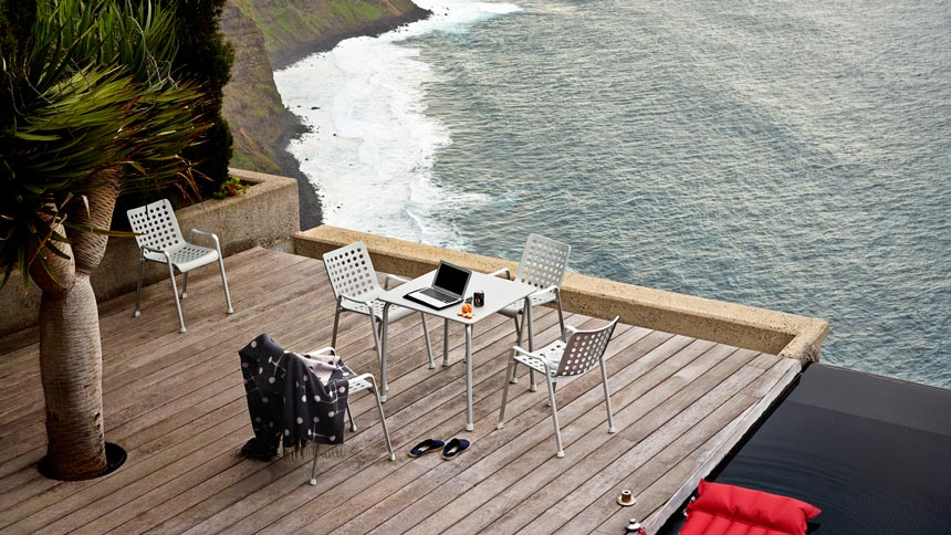 A large decked veranda overlooking the sea with an outdoor dining setup looks amazing. Image by Nest.co.uk.