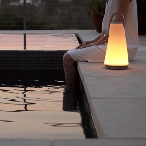 A woman sitting by the edge of a pool with her feet inside the water and a portable light besides her after sunset hours creating a soothing ambiance. Image by Nest.co.uk.
