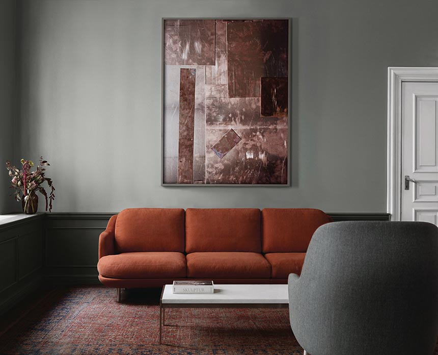 A rusty colored round and curvy sofa. One of 2018 sofa trends. The whole room has a minimal but deep, saturated moody color palette, making the sofa a real understated accent. Image by Nest.co.uk.
