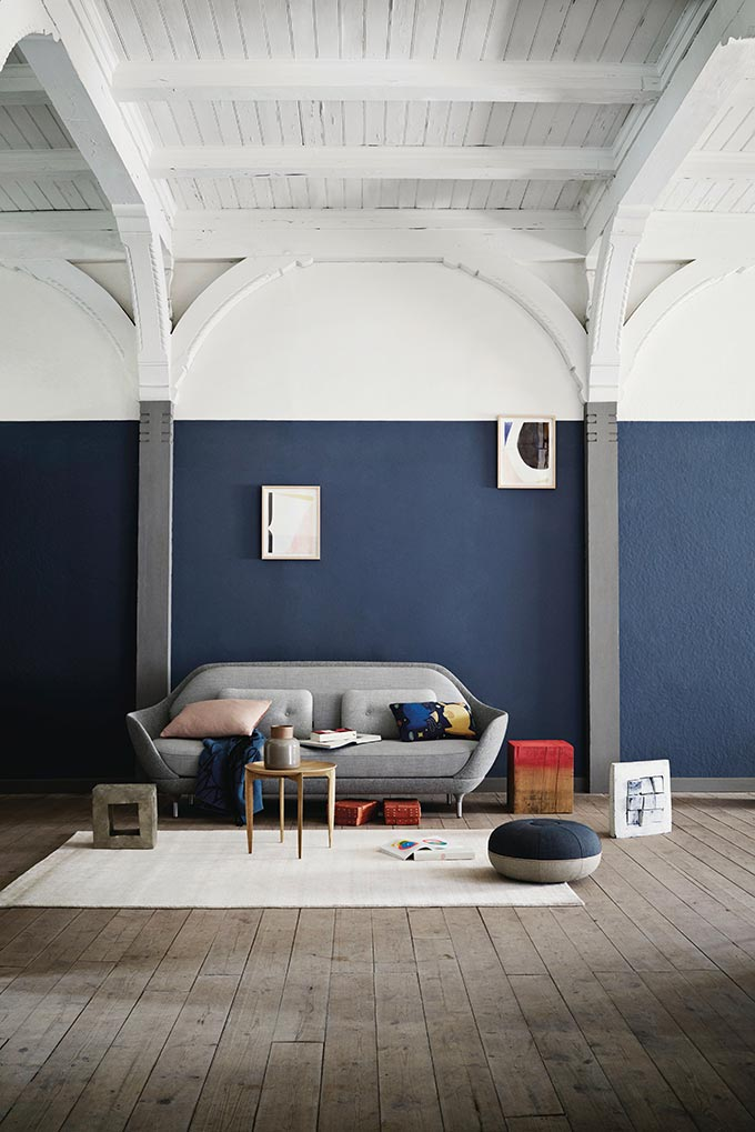 A fabulous curvy gray sofa against a color blocked white and navy blue wall. Its all styled in a very casual but inviting way. Image by Nest.co.uk.