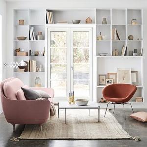 Curvy sofas, one of the 2018 sofa trends. A very stylish white room with built in bookcases around a window door, a pink curvy sofa, an airy coffee table and a rusty colored armchair as the perfect accent. Image by Nest.co.uk.
