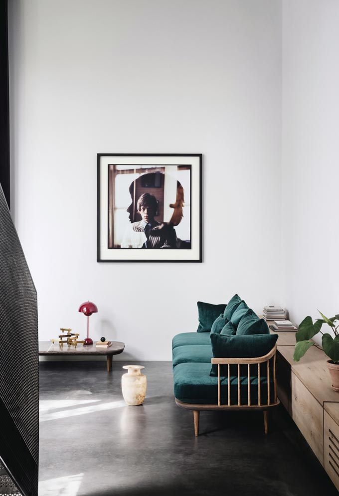 A dark green velvet wooden sofa in a contemporary minimal interior looks warm and inviting. Image by Nest.co.uk.