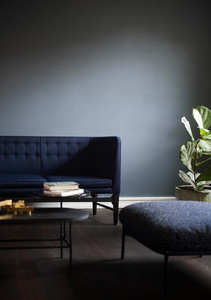 One of the 2018 sofa trends. Partial view of a dark blue sofa with a high back in a minimal interior. Image by Nest.co.uk.