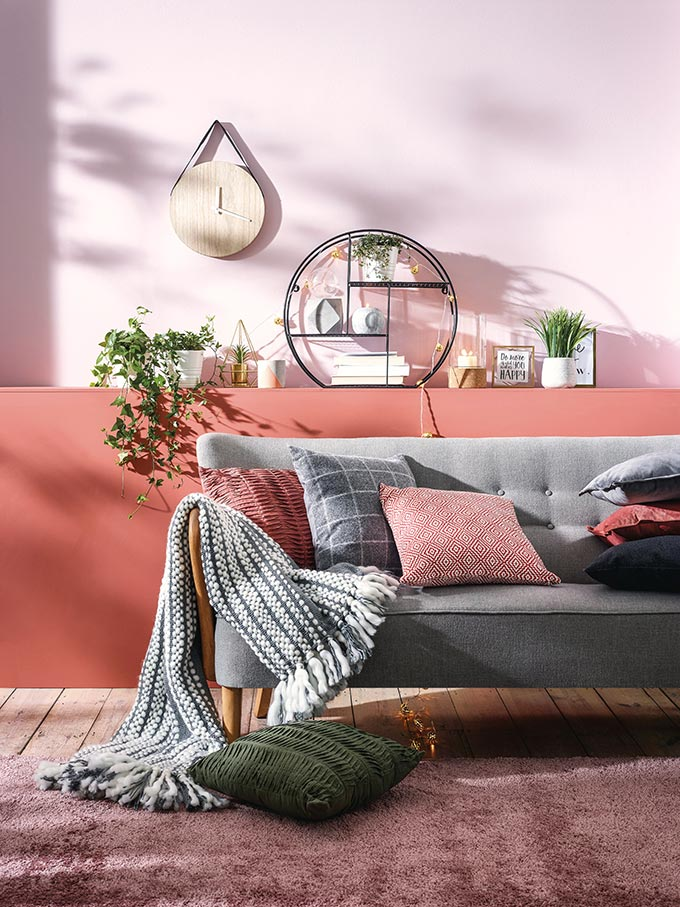 A cozy and stylish sitting room where rusty hues and greys contrast. A grey sofa against a color blocked accent wall would look sterile if it wasn't for the decor and especially the textiles to give it a homey feeling. Image by Primark UK.