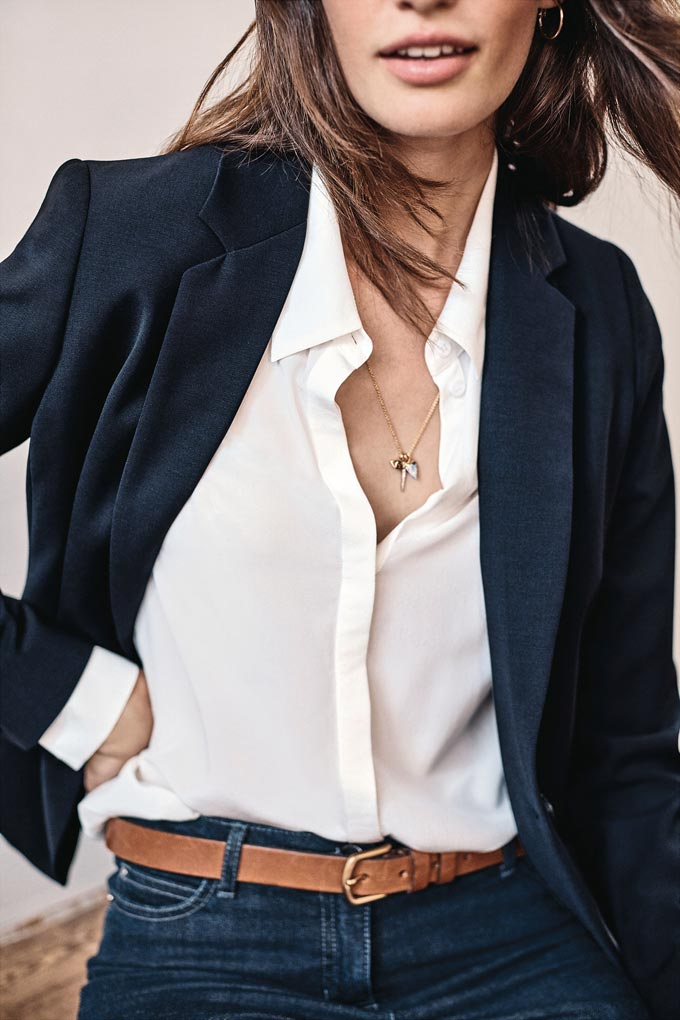 A close up of a chic woman dressed with an off white shirt, black tailored blazer jacket, and dark blue pants with a tanned thin leather belt around the waist. Image by PureCollection.