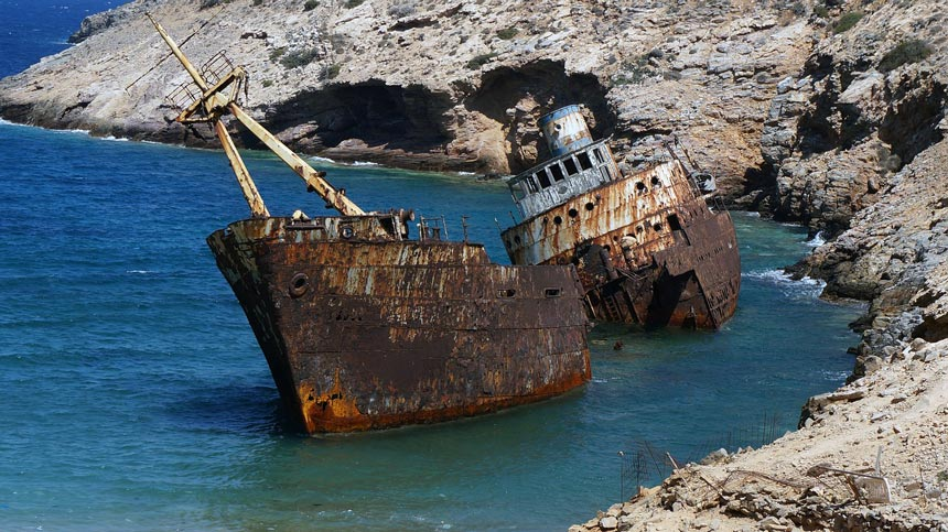 A rusty ship-wreck by the coast of a cove in the Greek island of Amorgos.