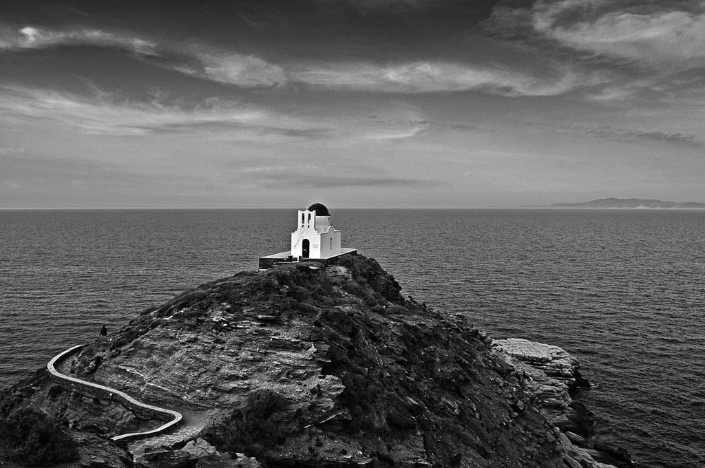 A black and white image of a Greek chapel on top of a rocky cliff on the island of Sifnos. Image by Marina Vernicos.