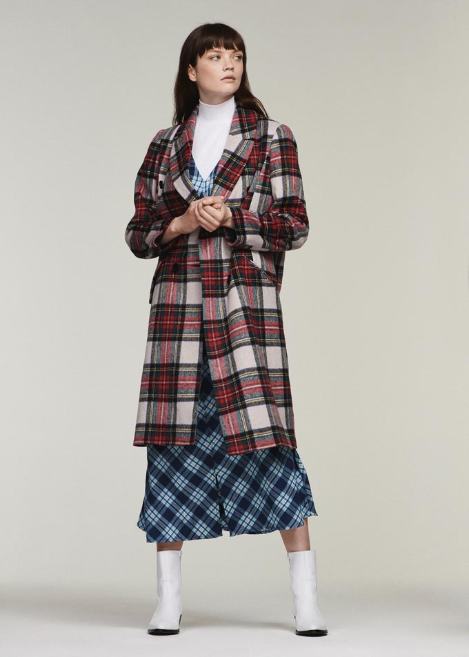 A red plaid coat over a plaid dress. A funky combo worn by a brunette woman. Lifestyle image by Debenhams.