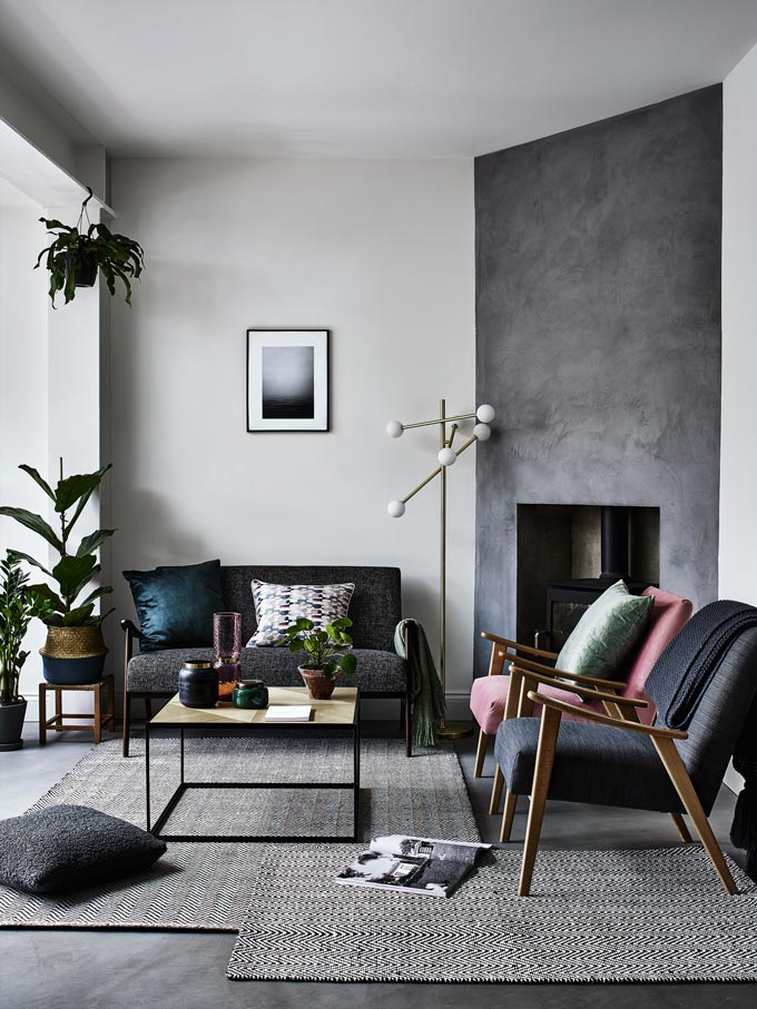 A contemporary Nordic grey interior with an accent concrete fireplace in the corner. I just love the mix of different grey hues, accent colors when it comes to textiles and different wood stain colors. Image by Debenhams.