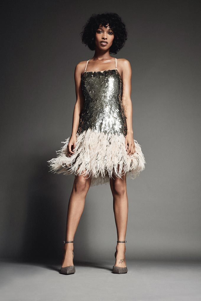 A stylish woman dressed formally in a silver sequin dress with spaghetti straps and white feathers skirt, in high heels. Image by Debenhams.