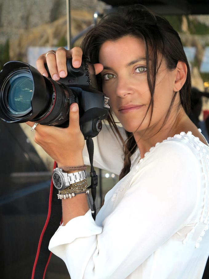 A portrait image of Marina Vernicos holding her camera while in a photo shoot.
