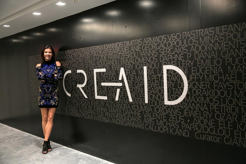 Marina Vernicos standing in front of a wall sign that reads CREAID.