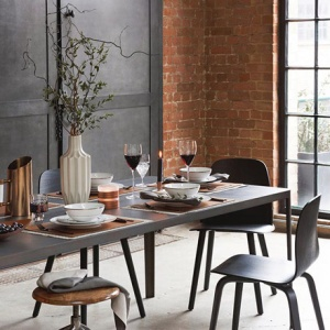 An industrial dining setting with a brick accent wall in the background. Image by Amara.