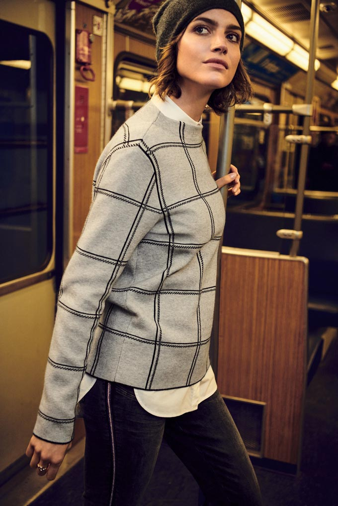 I love this not typical check pattern of this grey sweater a stylish young woman wears in an old train car. Image by Betty & Co.