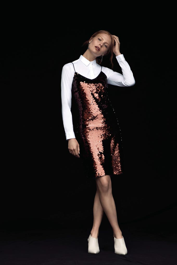 A cool outfit! A woman dressed with a white shirt and white booties is wearing a copper colored sequin dress with spaghetti straps over it. Layer and glow! Image by Dorothy Perkins.