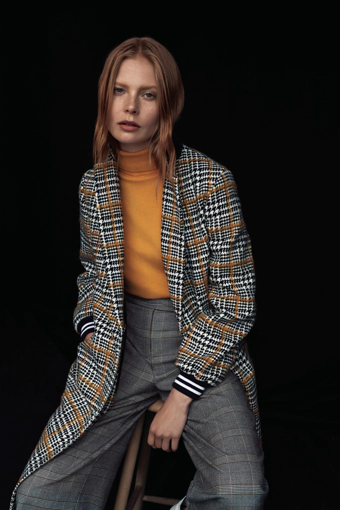 The tartan coat is probably the hottest new staple to buy this fall. A beautiful woman wears it casually over grey plaid pants and an ochre pullover. Image by Dorothy Perkins.