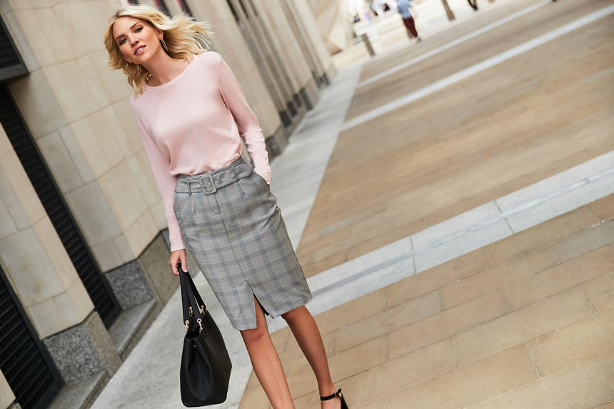 A great uniform for work: A pink top with a plaid grey skirt as worn by this blonde woman down the street. A lifestyle image by Dorothy Perkins.
