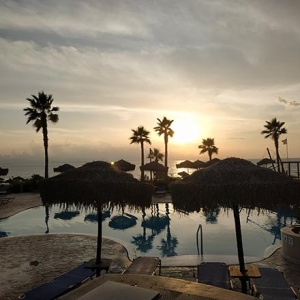 Gorgeous! An idyllic view of the pools and the sea shore at sunset hours. The shadows of the palm trees reflect upon the pool's water.