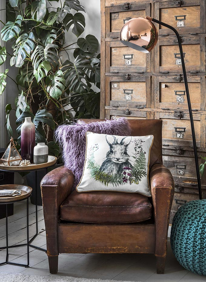 A vintage looking vignette with a leather armchair, a huge plant behind and an vintage tall chest of drawers. A copper floor lamp fills in nicely this vignette. Image by George Home at Asda.