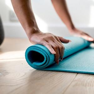 A woman rolling a yoga mat.