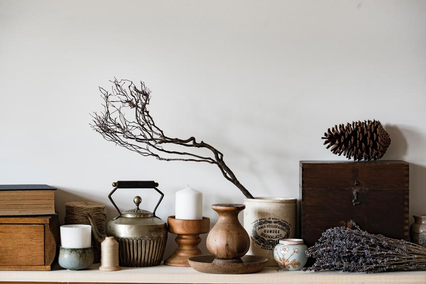 Earthly decor (teapots, candlestics) aligned against a white background.