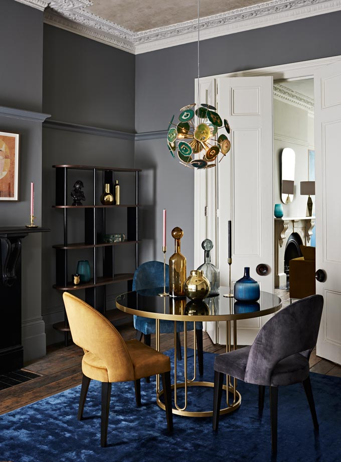 A beautiful formal dining space with a glass top round dining table, velvet dining chairs in various colors and a stunning pendant light. Image by John Lewis.