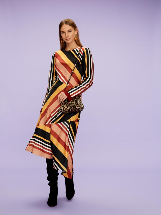 What a combo! A striped rainbow dress with a leopard print bag and slouch suede Monsoon leather boots. Image by Littlewoods.
