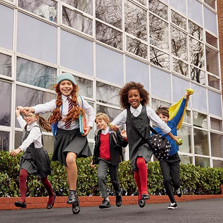 School children running outside a school building. Image by Marks & Spencer.