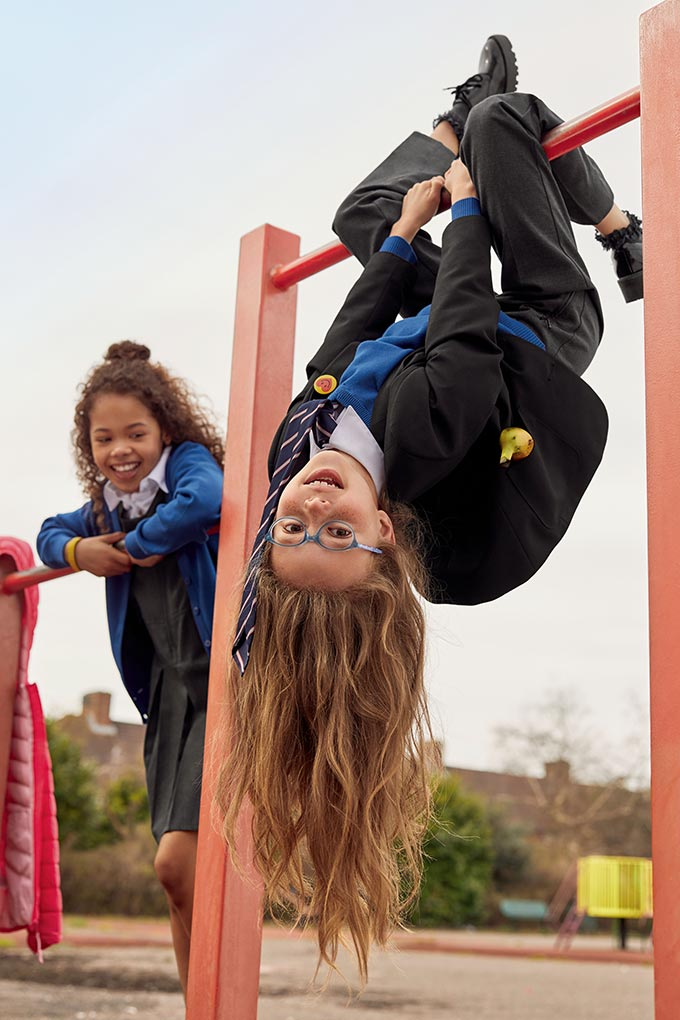 Two school girls playing at a playground's frames. Image by Marks & Spencer.