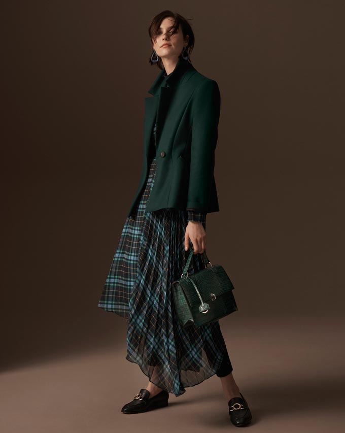 A stylish woman dressed with a casual long tartan blue and green print dress. A solid colored dark coat is just the right fit. Image by Marks and Spencer.