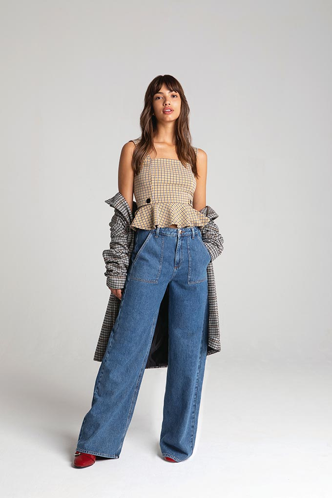 A love the wide leg denim pants paired with a check top and a plaid coat. Lifestyle image by Miss Selfridge.