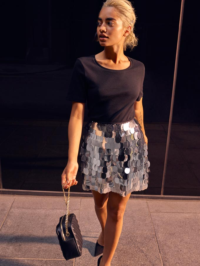 Love the style - a black top with a silver sequin skirt and black handbag worn by a woman walking down a street. Image by Miss Selfridge.