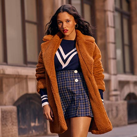 A stylish young woman wears a mini tartan print skirt with a dark blue sweater and a rusty colored faux teddy coat as she walks down the street. Image by Miss Selfridge.