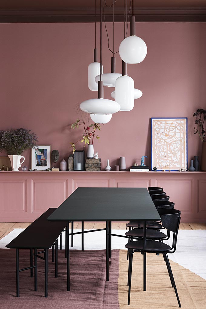 A black dining table and chairs against a muted pink wall. Image by Nest.