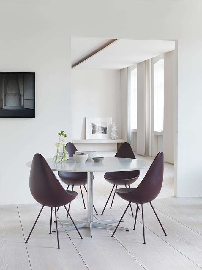 A stylish minimal dining space with a round dining table and Fritz Hansen's plastic Drop chairs. Image by Nest.